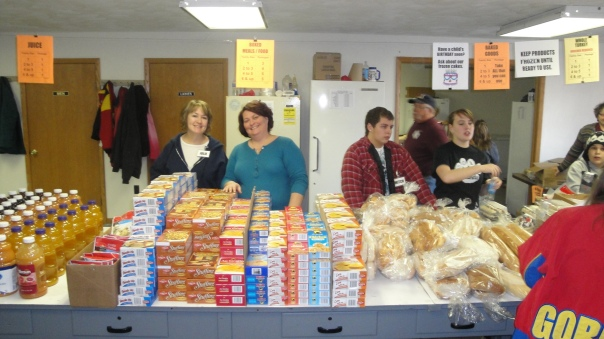 volunteers helping people pick out food during a distribution